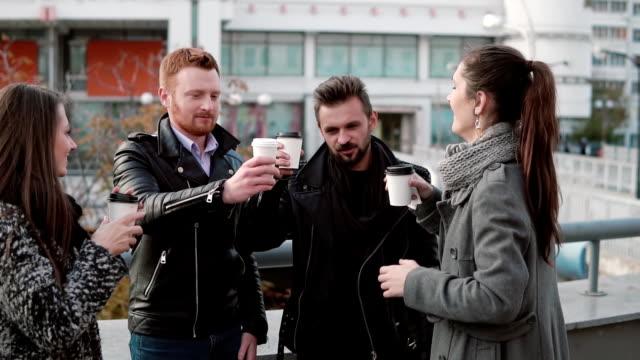 Four beautiful young people joyfully clink cardboard cups standing near a bridge railing. Slow mo video