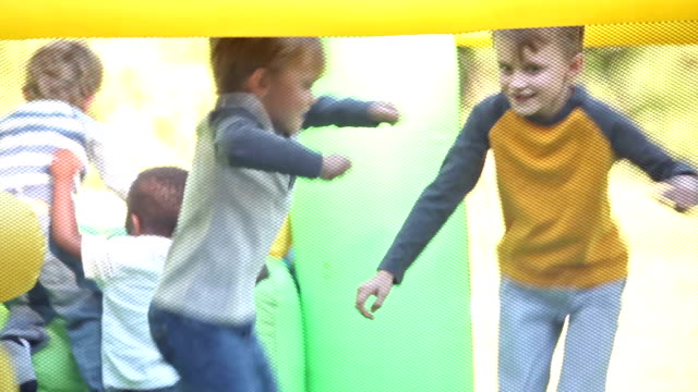 Four boys jumping in a bounce house video