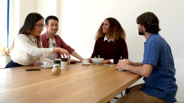 stockvideo's en b-roll-footage met vier mensen uit het bedrijfsleven in discussie op cafe - 20 29 jaar