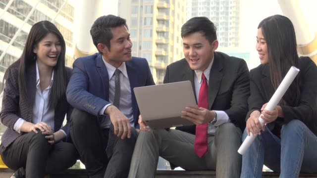 Four Business Person Consult On Laptop Outdoor