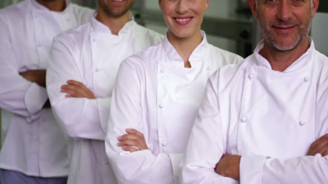 Four cheerful chefs looking at camera with arms crossed video