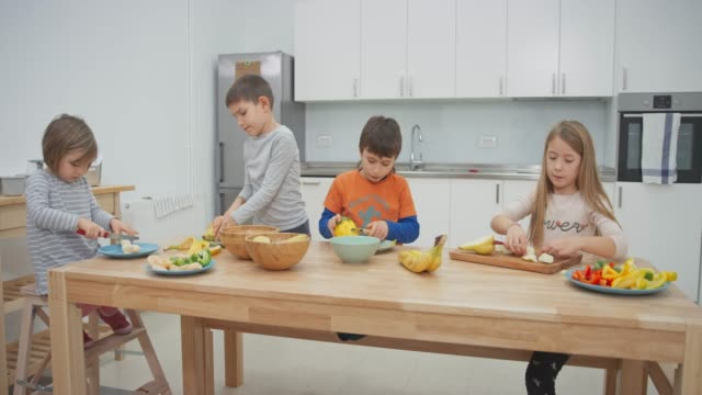 Four children cutting fruit at the table in the kitchen