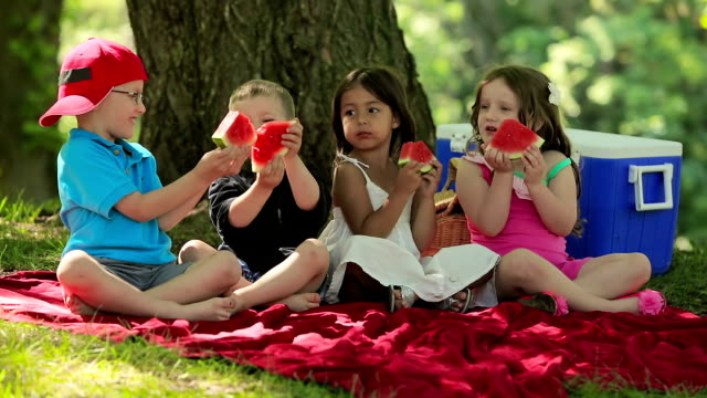 Four children have fun eating fruit together video