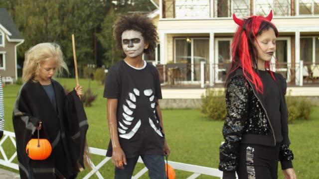 czwórka dzieci w kostiumach na halloween party - four seasons filmów i materiałów b-roll