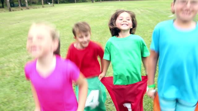 Four children in park having potato sack race video