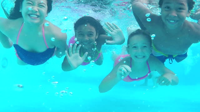 Natación submarina cuatro hijos hacia la cámara - vídeo
