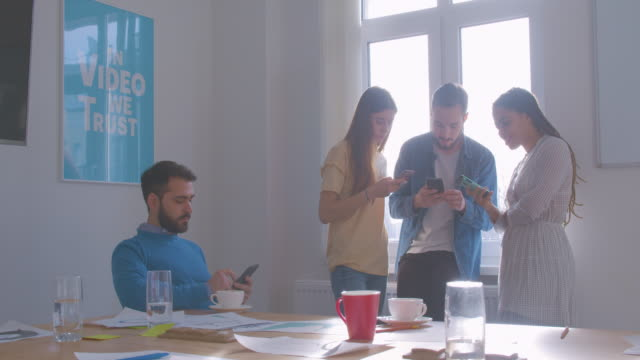 Four diverse multi-racial colleagues at office coffee break use smartphone modern internet problem