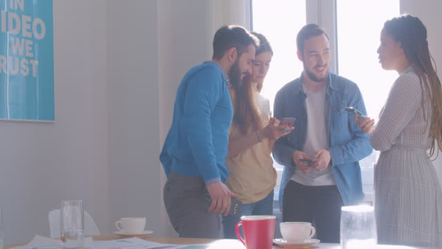 Four diverse multi-racial colleagues at office coffee break use smartphone internet laughing video joke