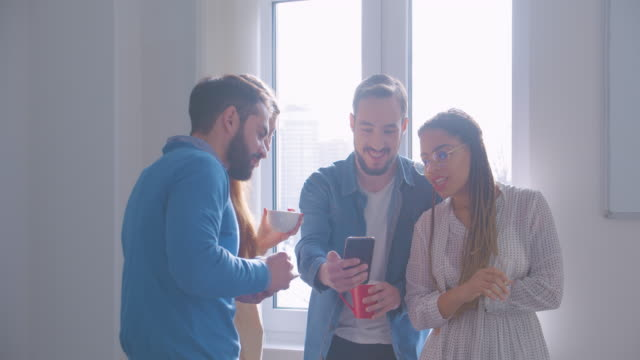 Four diverse multiracial colleagues in office break coffee conversation smartphone