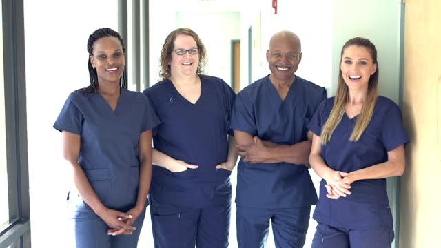 four doctors or nurses working in hospital - fianco a fianco video stock e b–roll