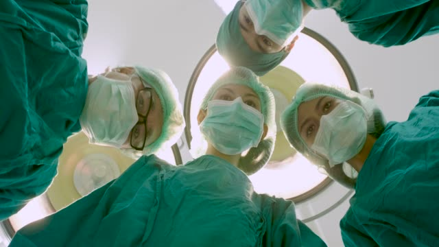 POV four doctors wearing full surgical scrubs looking at the patient in operating theater at the hospital.