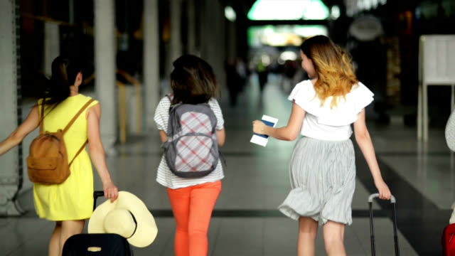 vídeos de stock e filmes b-roll de four female friends in bright summer clothing are late for their plane. beautiful girls are running inside the airport with documents, tickets, and large suitcases in hands - amizade feminina