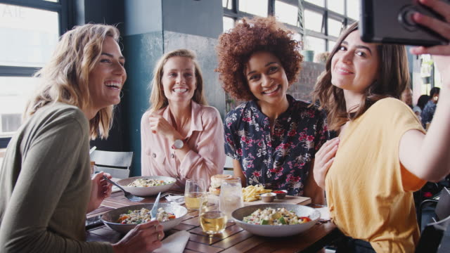 Four female friends sitting around restaurant table posing for selfie - shot in slow motion