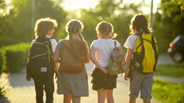 four friends are going to school. they have a lot of fun because today is their first day at school - scolaro video stock e b–roll