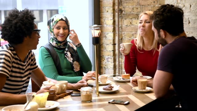 Four friends in cafe with hot drinks and sharing cookie video
