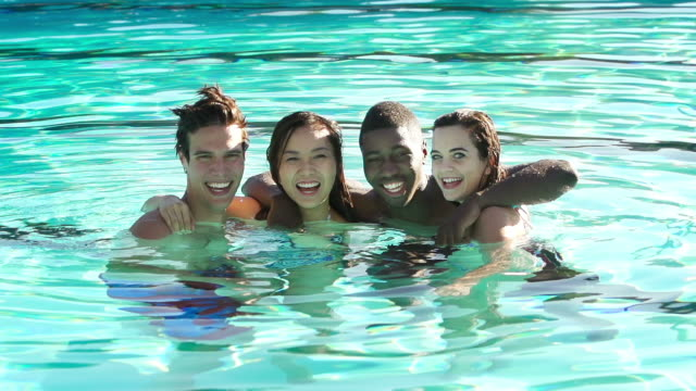 Four friends swimming at an outdoor pool video