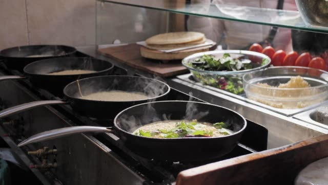 four frying pans with steam in restaurant kitchen. cooking classical jewish yemenite food. making lachuch. slow motion. beautiful cinematic steam on sunlight - busy restaurant kitchen stock videos & royalty-free footage