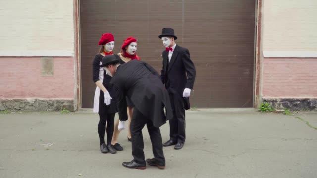 four funny mimes play scenes on city street - гримировальные краски стоковые видео и кадры b-roll