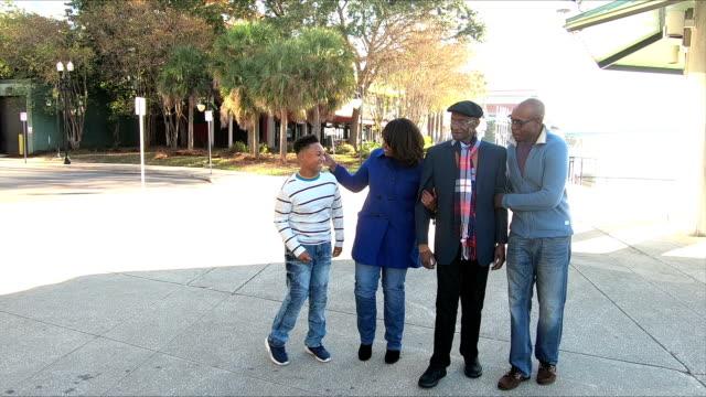 four generation african-american family walking - nonna e nipote camminare video stock e b–roll
