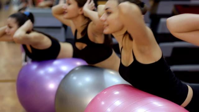 4 人の女の子は、ジムでのフィットネス ボールでスポーツを行います。 - 有酸素運動点の映像素材/bロール