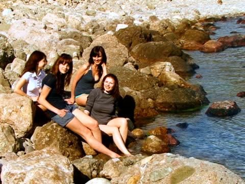 vídeos de stock e filmes b-roll de quatro meninas na praia - só mulheres jovens