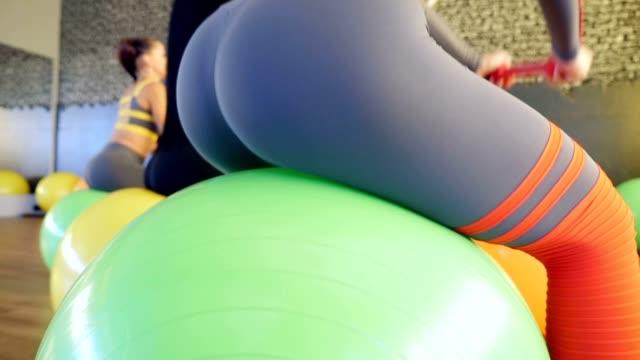 fyra flickor tränar skinkor hoppning på bollar i gymmet - bum bildbanksvideor och videomaterial från bakom kulisserna
