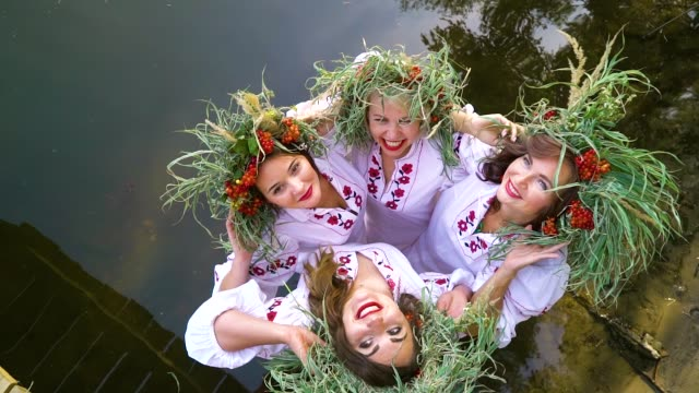 four happy girls in floral circlets and embroidered dresses posing in water - славянская культура стоковые видео и кадры b-roll