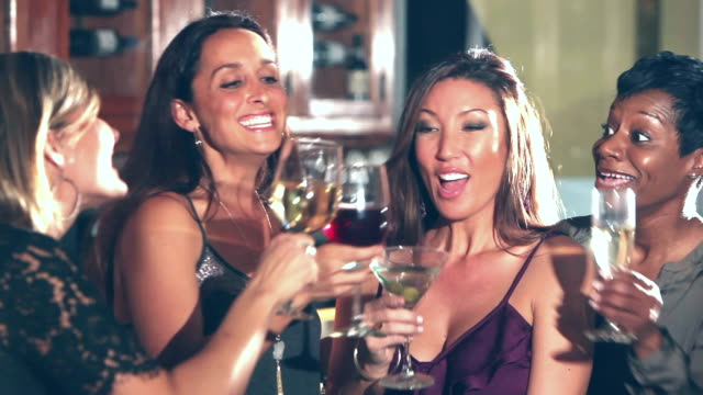 Four happy multi-ethnic women drinking at a party A group of four cheerful multi-ethnic women in their 30s at a party smiling, conversing and drinking wine and cocktails. It is ladies night out. They raise their glasses for a celebratory toast. girlfriend stock videos & royalty-free footage