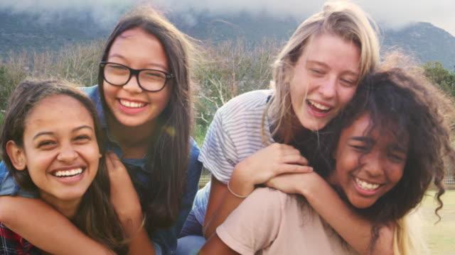 vídeos de stock e filmes b-roll de four happy teenage girls piggybacking outdoors, close up - etnia