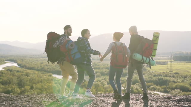 Four hipster friends holding hands and running to the mountain