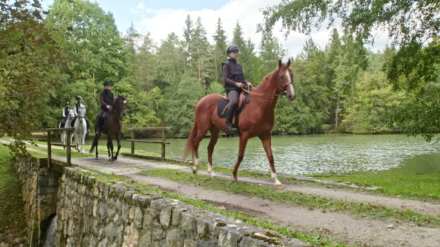 CS Four horseback riders riding on bridge across lake