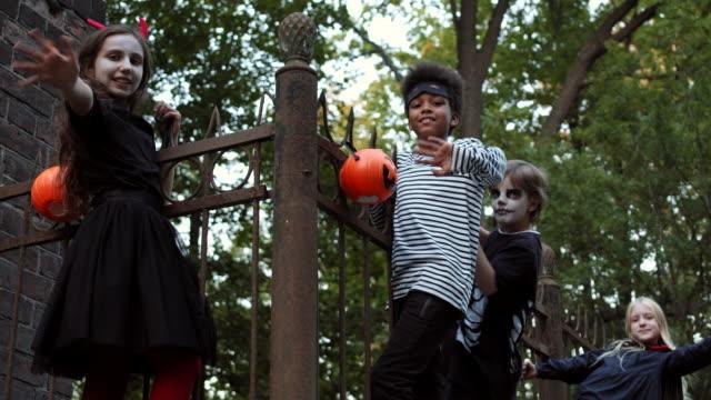 cztery dzieci wiszące na ogrodzeniu na halloween party - four seasons filmów i materiałów b-roll