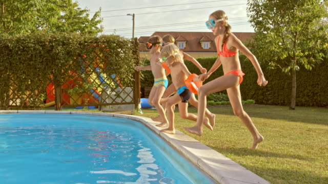 SLO MO TS Four kids jumping into the pool together video