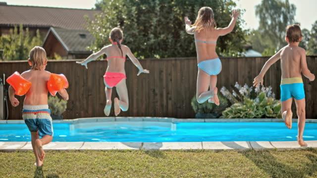 vídeos y material grabado en eventos de stock de cámara lenta de cuatro niños ds sumergiéndose en la piscina - backyard pool