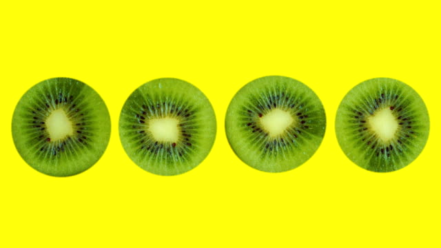 vídeos de stock e filmes b-roll de four kiwis, cut in half, rotate on a yellow background. isolated. concept. - kiwi