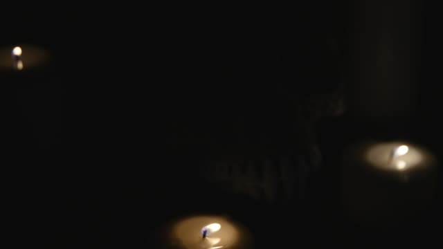 four lighted candles and a skull on a black background. close up video