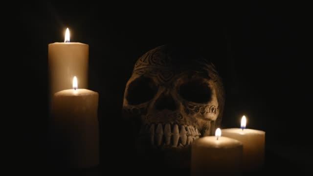 stockvideo's en b-roll-footage met vier brandende kaarsen en een schedel op een zwarte achtergrond - swearing