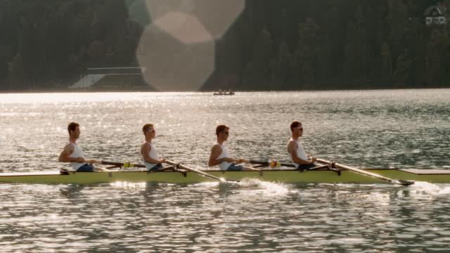 SLO MO TS Four male athletes rowing across the lake at sunset video