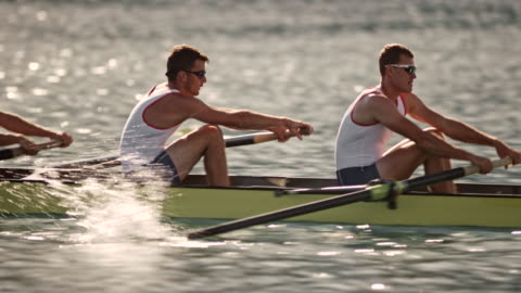 TS Four male athletes rowing on a lake Wide tracking shot of four male athletes rowing on a lake in a coxless four boat. Shot in Slovenia. competition stock videos & royalty-free footage