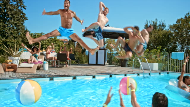 Four men jumping into the pool together at a pool party while their friend cheer for them