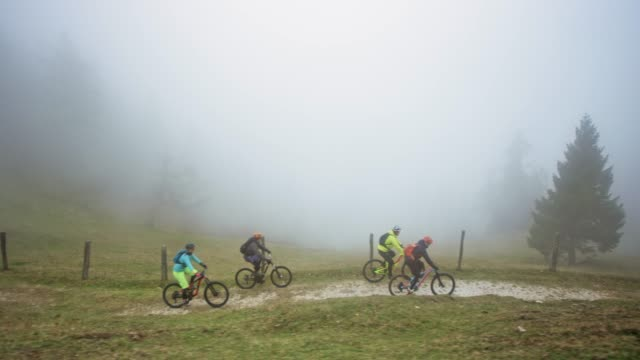 Four mountain bikers riding down a mountain trail in heavy fog