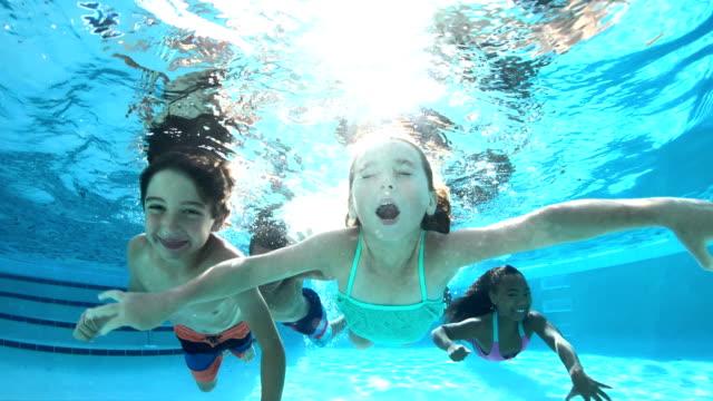 vier multi-ethnischen kinder schwimmen unter wasser im pool - ferienlager stock-videos und b-roll-filmmaterial