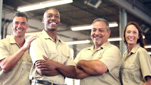 vidéos et rushes de quatre ouvriers multiethniques en entrepôt - uniforme