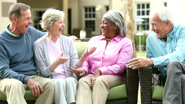 Four multi-ethnic seniors sitting on patio chatting video