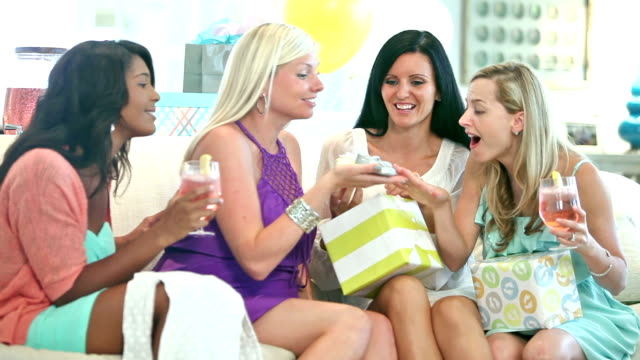 Four multi-ethnic women at baby shower opening gifts video