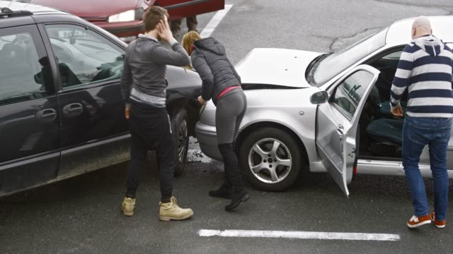 Four people assessing the damage at the  scene of the car accident Wide handheld shot of three men and a woman assessing the damage after the car accident. Shot in Slovenia. car accident stock videos & royalty-free footage