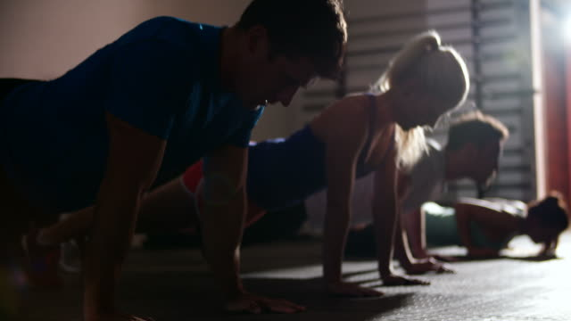 Four people doing press ups at a gym Four people doing press ups at a gym push ups stock videos & royalty-free footage