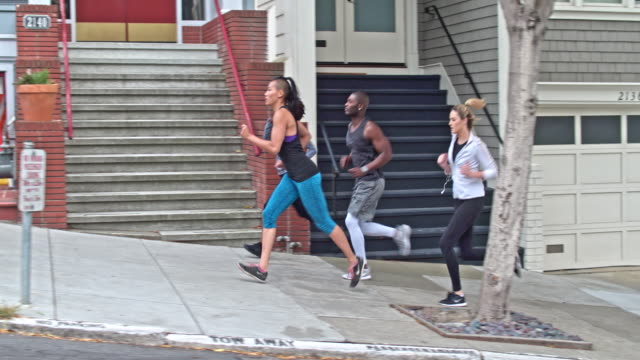 vídeos de stock e filmes b-roll de four people running in the streets of san francisco - young woman running city