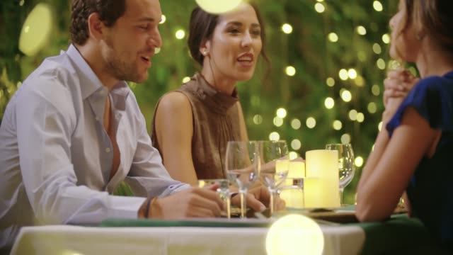 Four people, two couples happy talking and eating during a romantic gourmet dinner or lunch.Shiny lighting.Medium shot. Friends italian trip in Umbria.4k slow motion