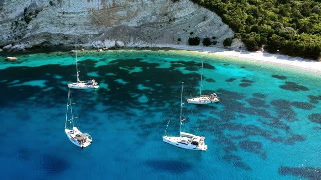 four sailboats moored at the bay - morze egejskie filmów i materiałów b-roll